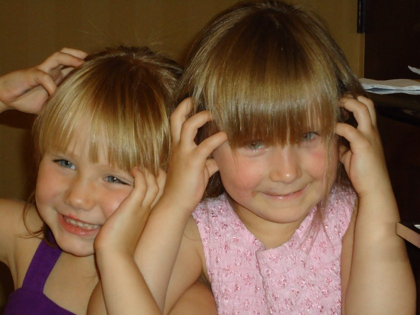 Little blonde girls scratching their heads