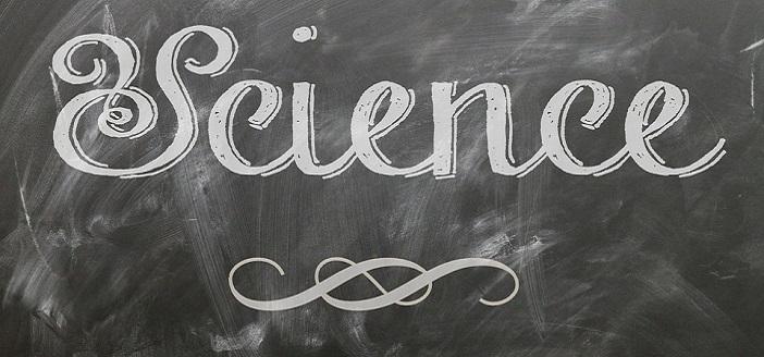 cursive white chalk letters on a blackboard chalkboard reading SCIENCE