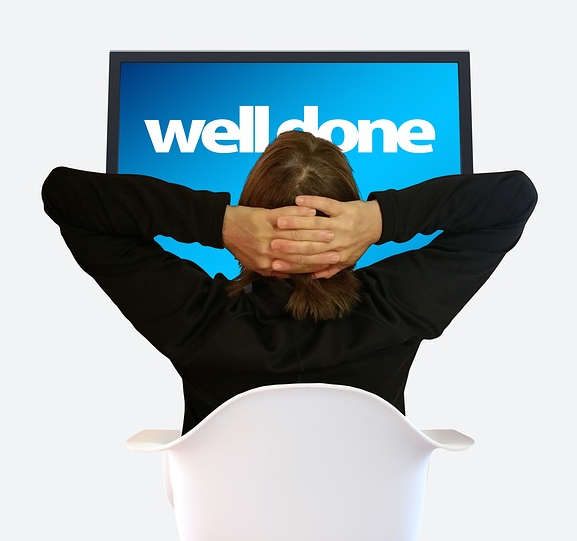 Rear view of someone leaning back in chair looking at a screen with words WELL DONE implying Job Satisfaction