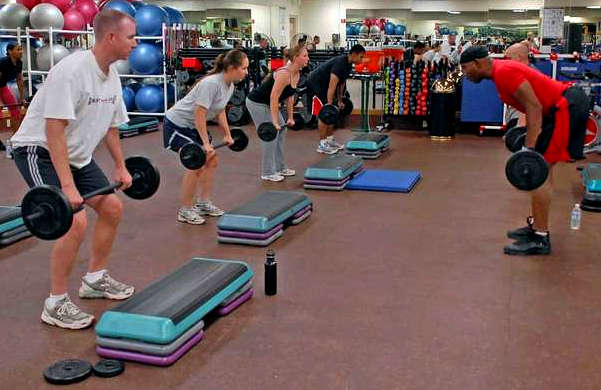 men and women working out with free weights barbells in a gym.