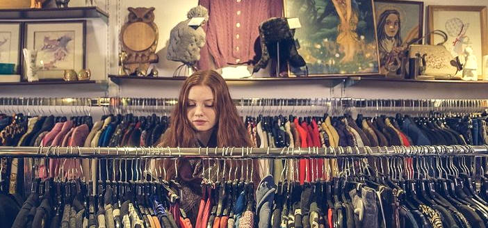 girl with long hair looking through clothes on a rack in a thrift store.