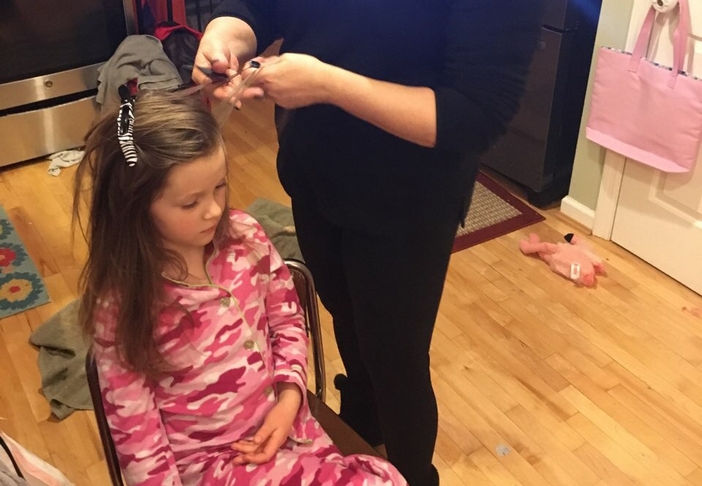 LiceDoctors Technician treating young girl with long brown hair and pink camo pajamas.