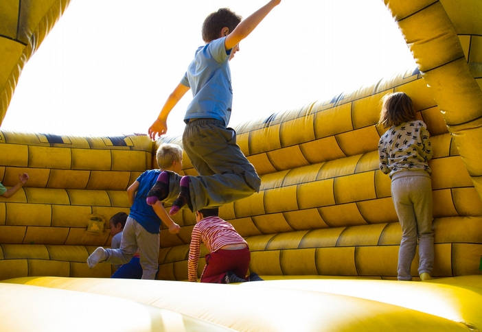 children bouncing in a yellow inflated bouncy house play room.
