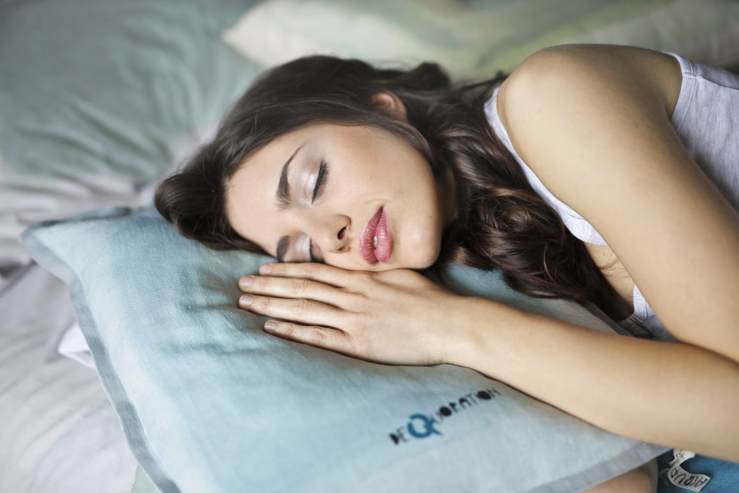woman sleeping peacefully cuddling pillow