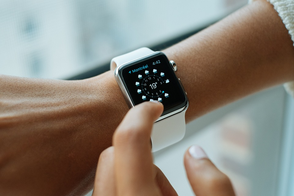 close image of a wrist watch with soft focus finger tapping at clock face.