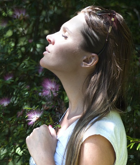 woman meditatively facing sky with eyes closed, soft focus greenery and purple flowers