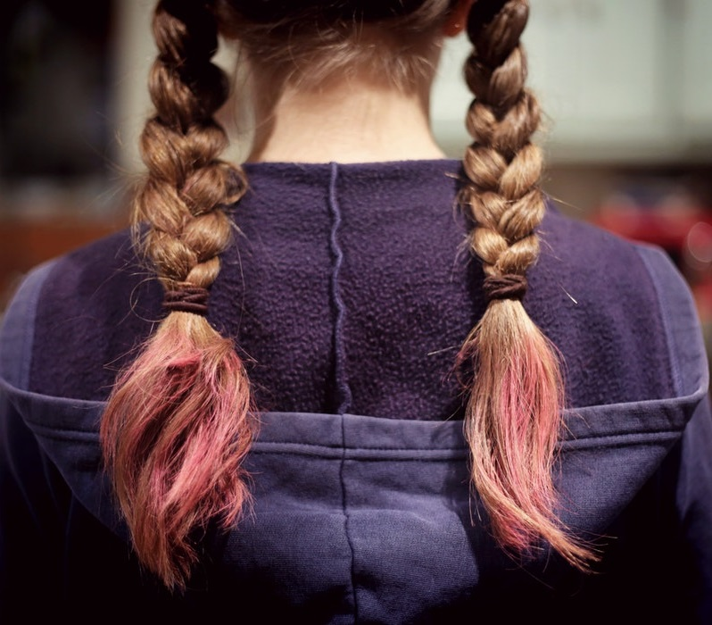 rear view of young girl with two braids brunette hair pink ends.
