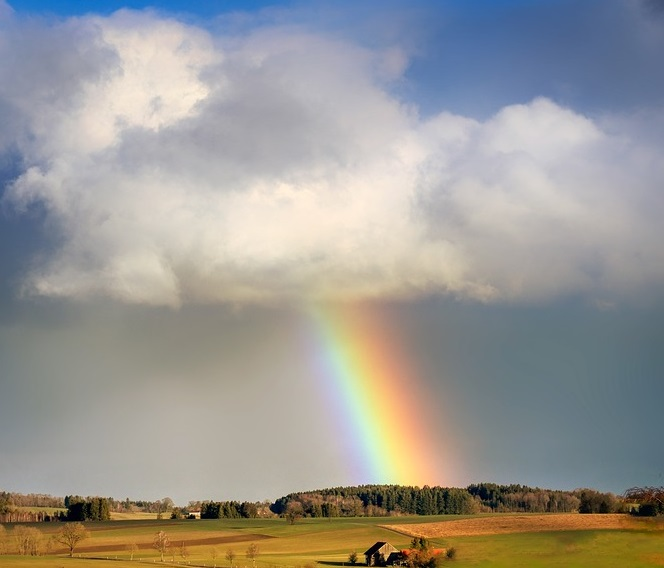 rainbow shining through clouds on to green pastoral farm