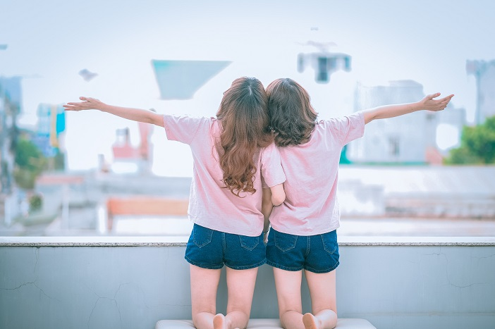 Rear view of two little girls looking out a large window, arms outstretched.