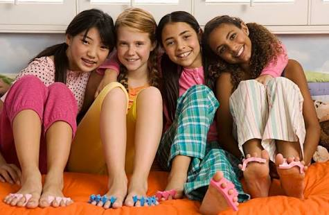 four girls sitting close together showing pedicures at slumber party