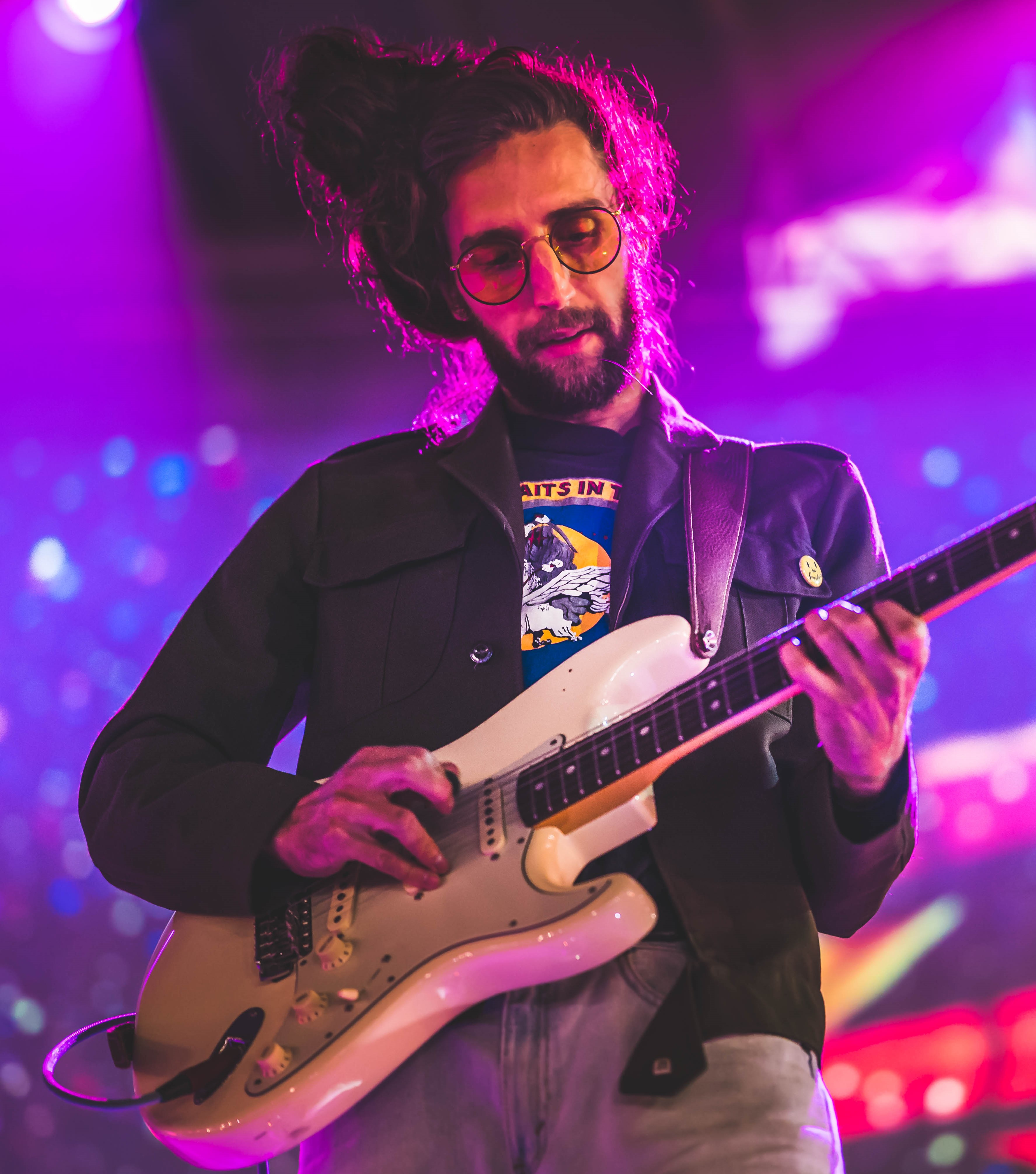Man wearing a leather jacket, glasses, and long hair in a bun on his head plays guitar on stage at Lumen 2019. There is a mixture of purple, blue, and pink lights behind him.