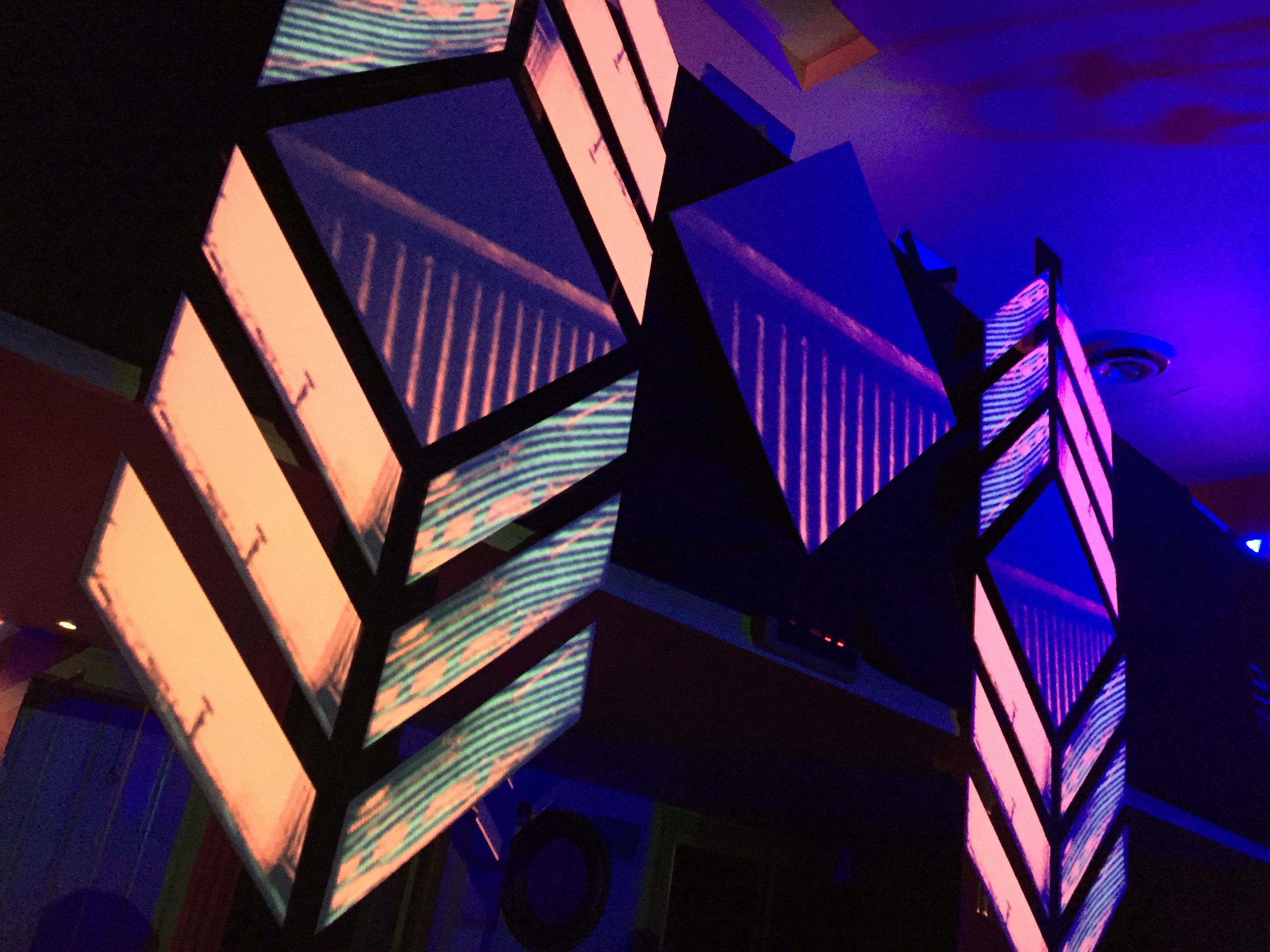 Geometric shapes including triangles placed on top of each other and lit up in yellows and purples