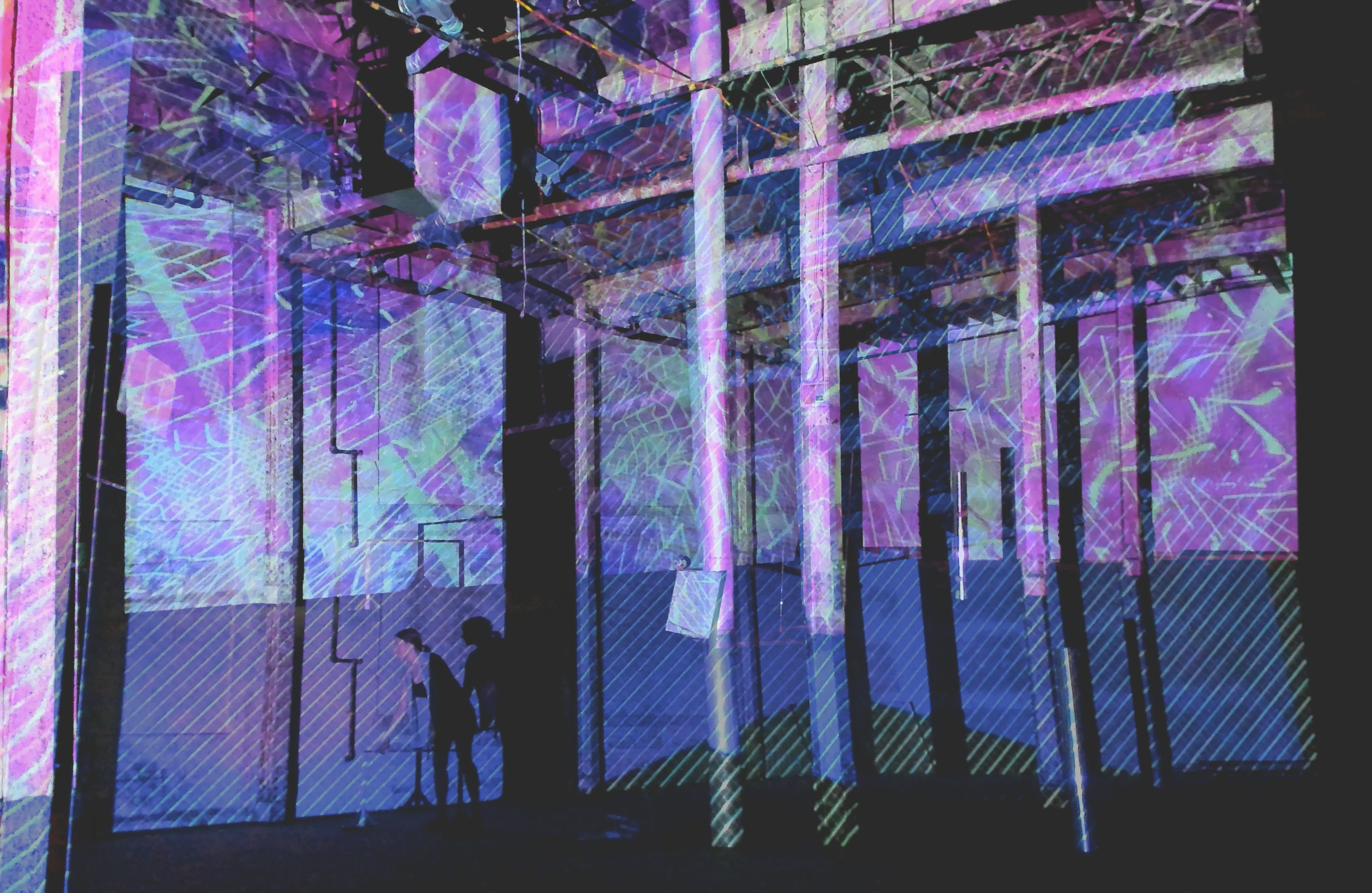 A person standing in an industrial room with pillars with a projection covering the walls