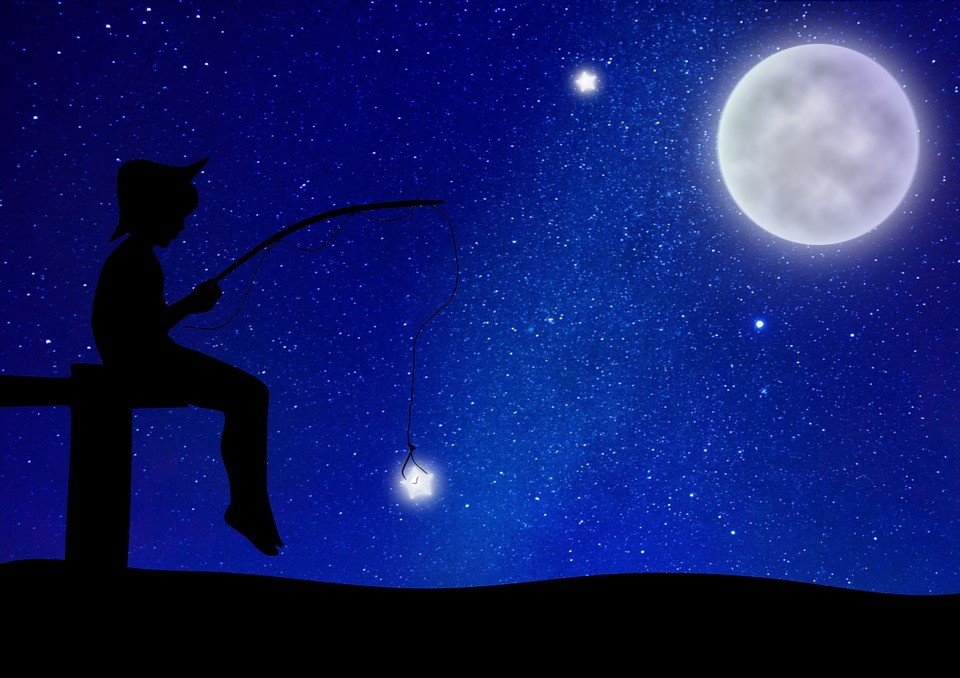 A person sitting in front of the night sky and holding a fishing rod as they catch a star