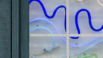 A window with a neon display of green, blue and white tubes