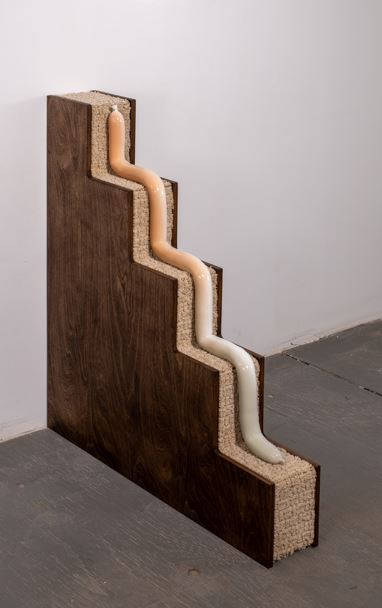 a wooden structure resembling thin stairs with carpet over each step and a ceramic tube going down it like a snake