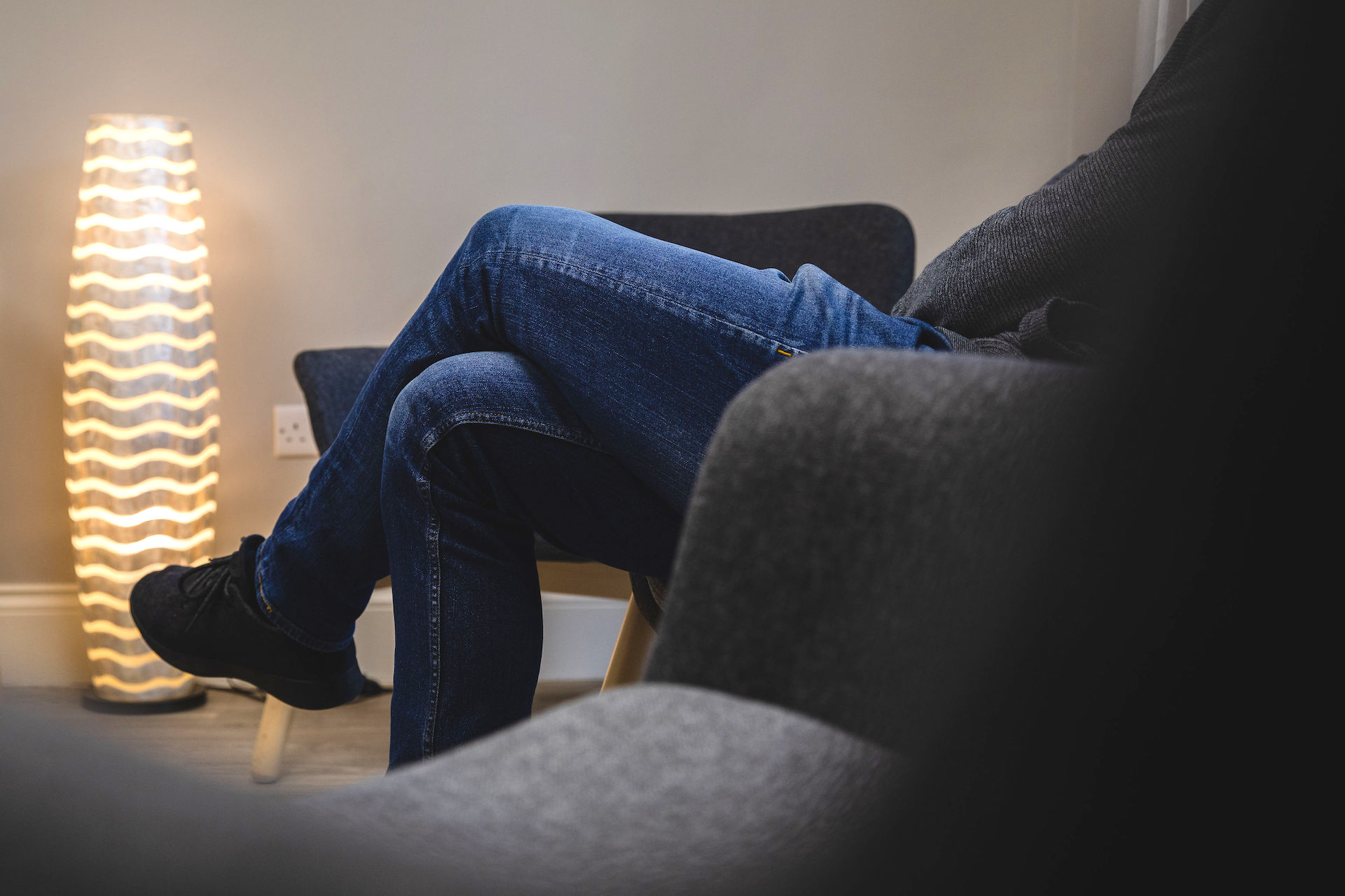 Man with legs crossed by lamp