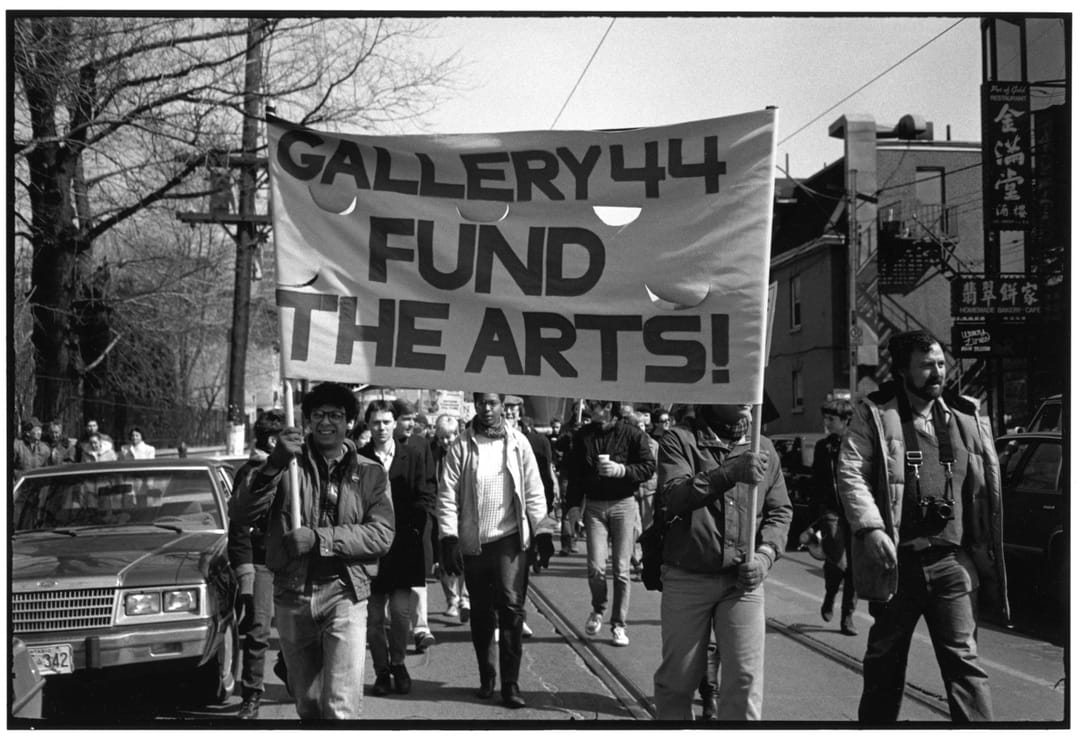 """A vintage photo of various people march down a city street, 2 persons are seen carrying a banner that reads """" Gallery 44 Fund the Arts"""""""
