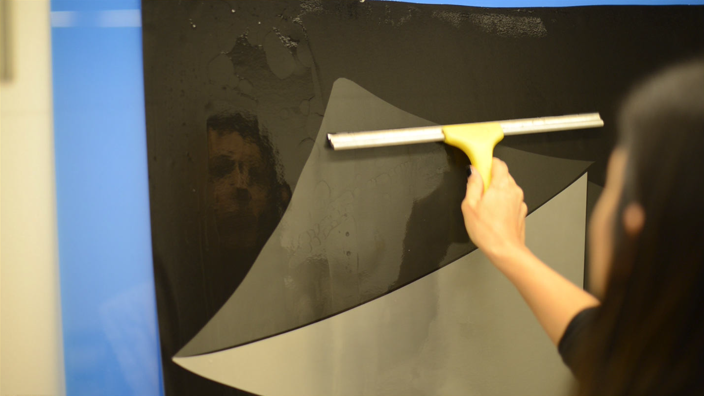 A person, wiping away excess water away using a squeegee on what looks like a large print.