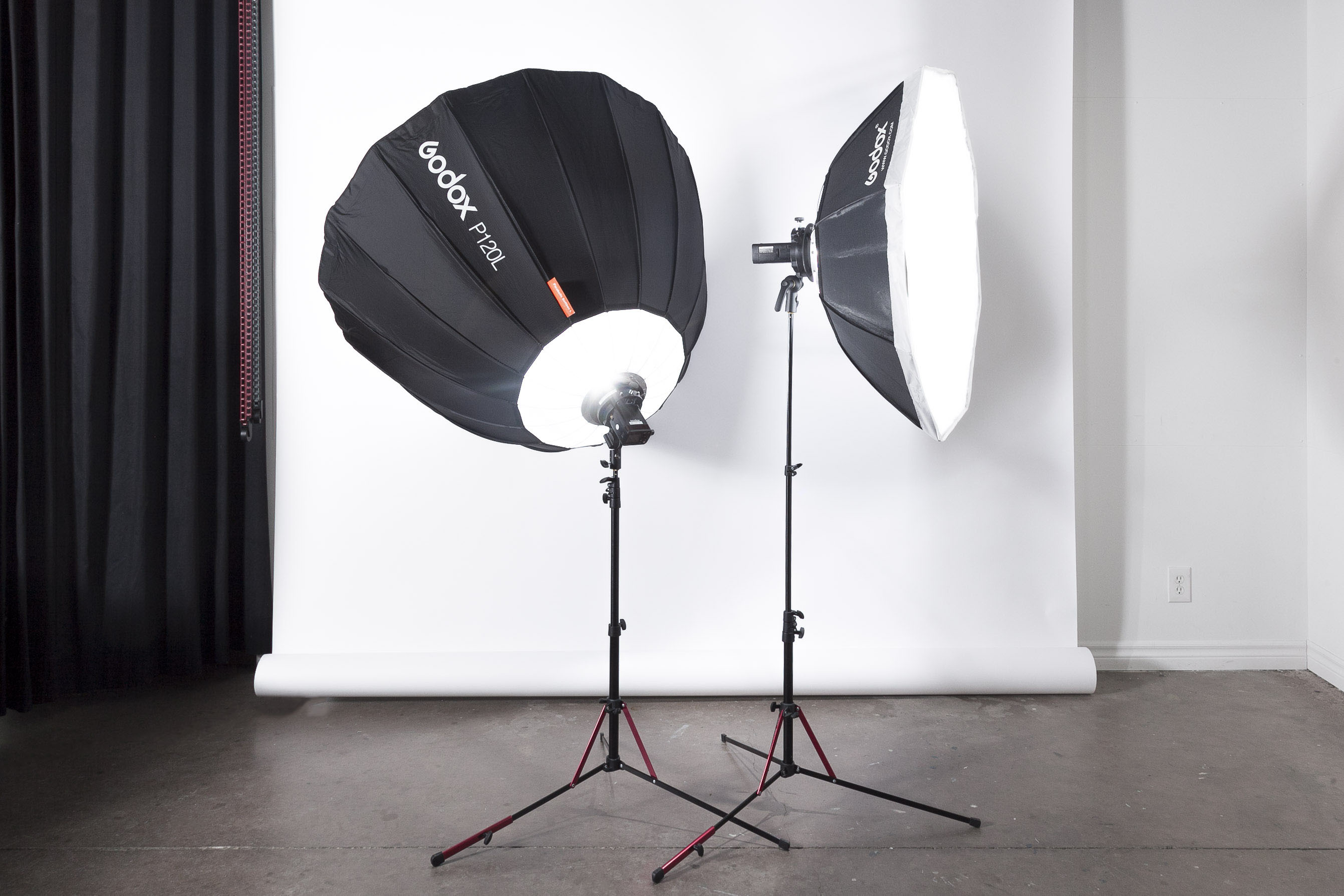Two Godox Studio Lights are each assembled and laced on a stand in front of a white photography backdrop in a studio.