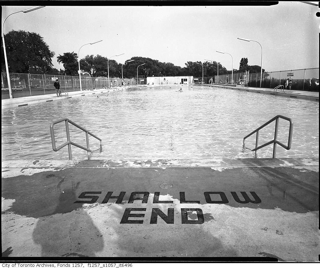"""And archival image of an outdoor swimming pool with the """"Shallow End"""" deck signage in the foreground"""