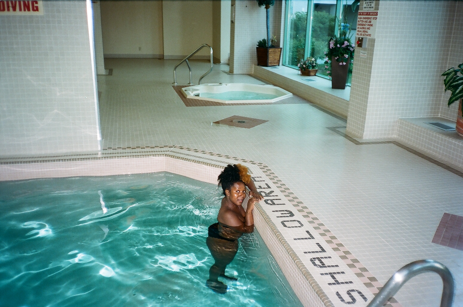 A colour snapshot of author in a swimming pool near the shallow end signage.
