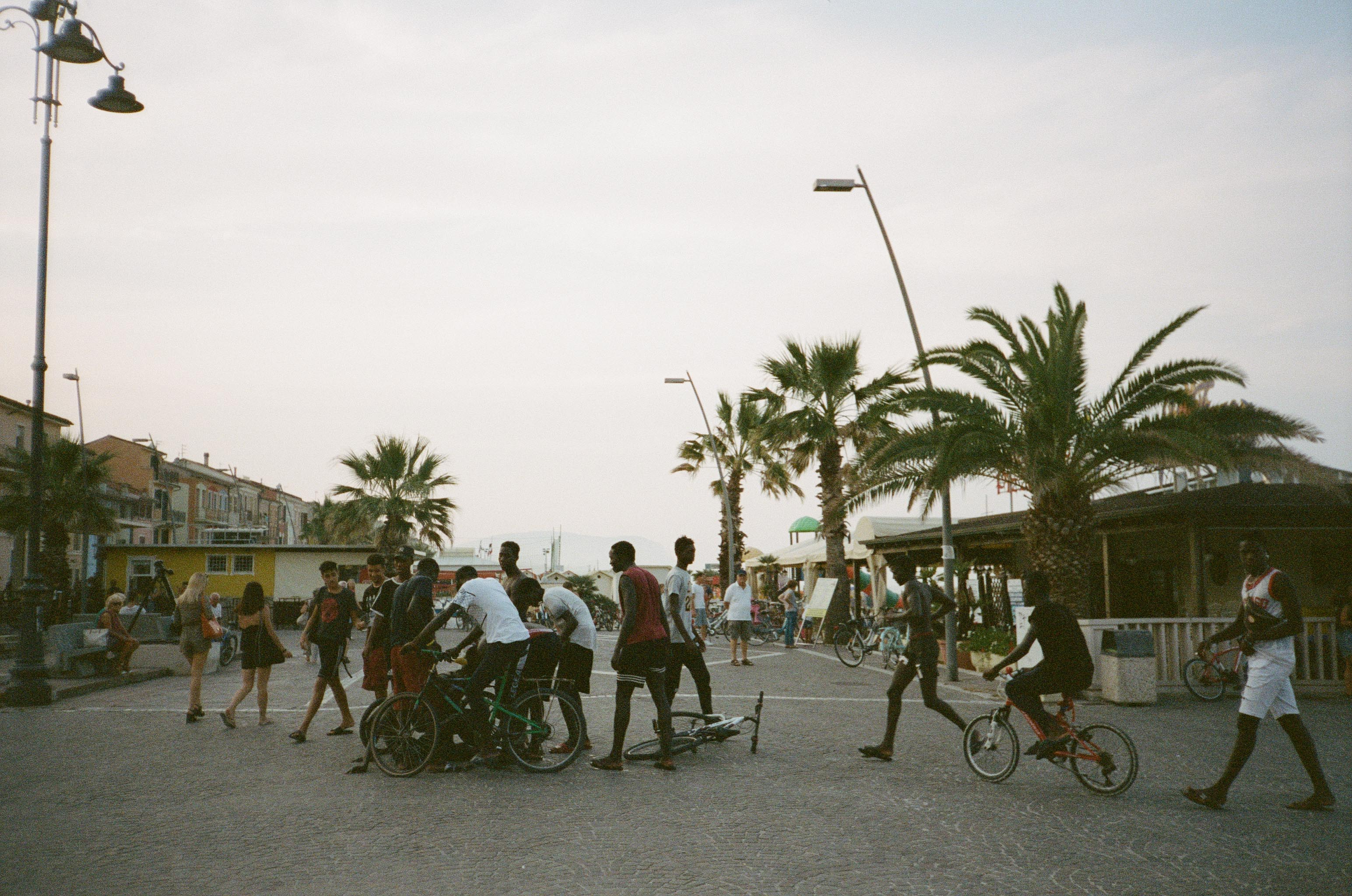 A busy scene at a beach boardwalk with a group of young Black men in the foreground.