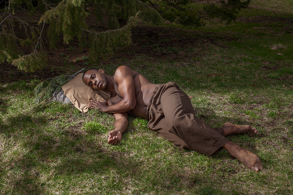 A image by Tavon Taylor of a man lying on a lawn, with no shirt as if ready to sleep.