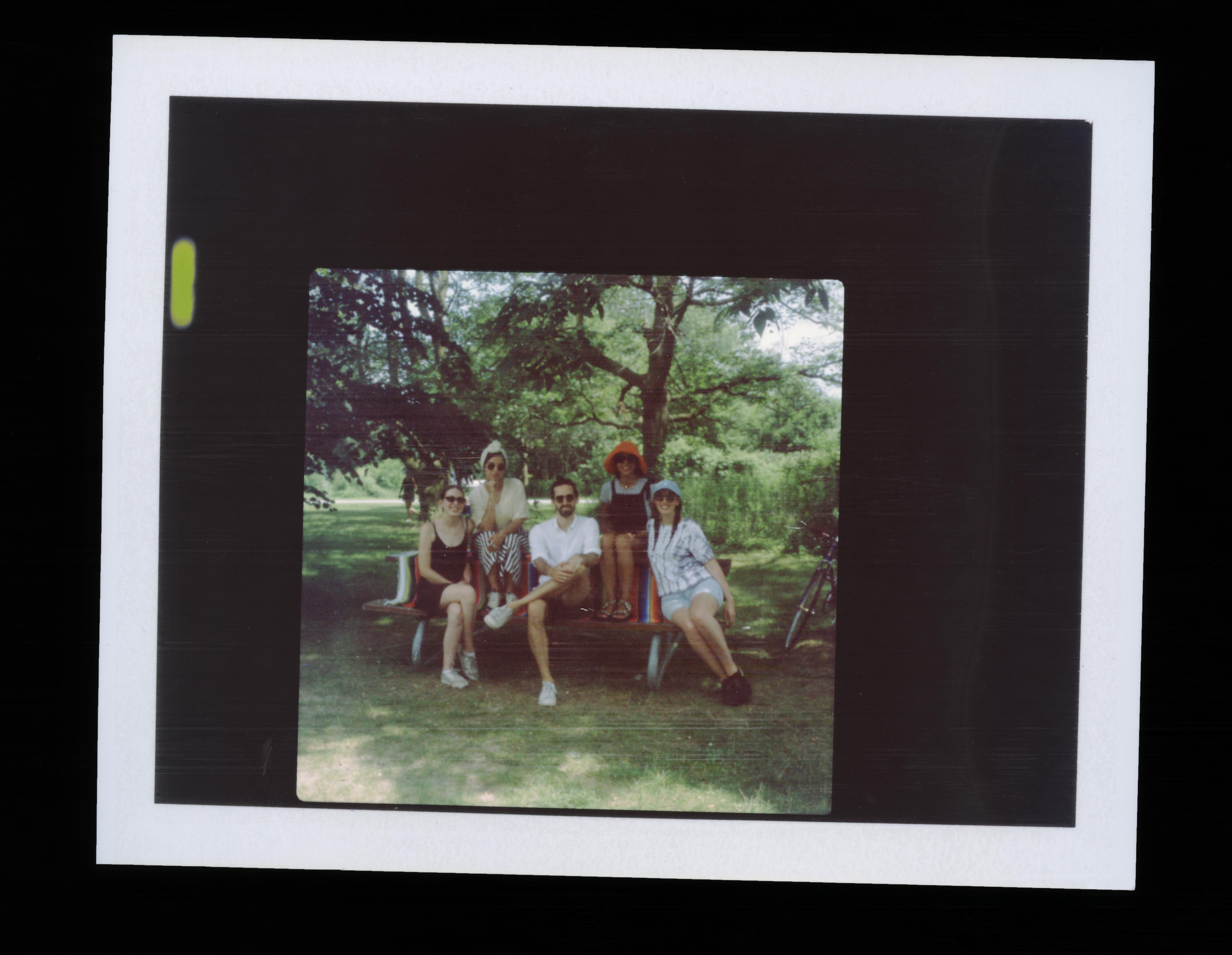 A instant film image of G44 staff sitting on a picnic table.