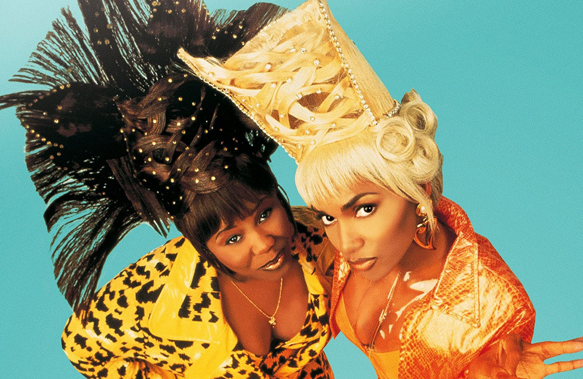 A promotional image for the film BAPS with Natalie Deselle-Reid and Halle Berry dressed in orange, with over the top hairstyles looking up at the camera.