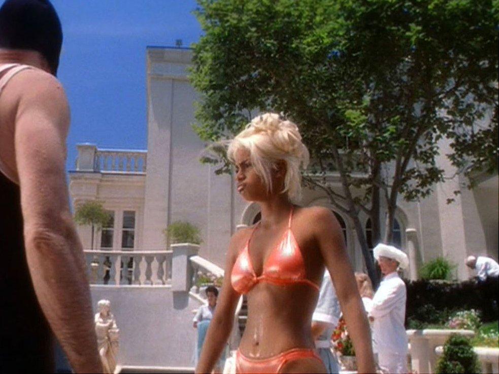 A screenshot from the film BAPS featuring Halle Berry in a orange bikini.