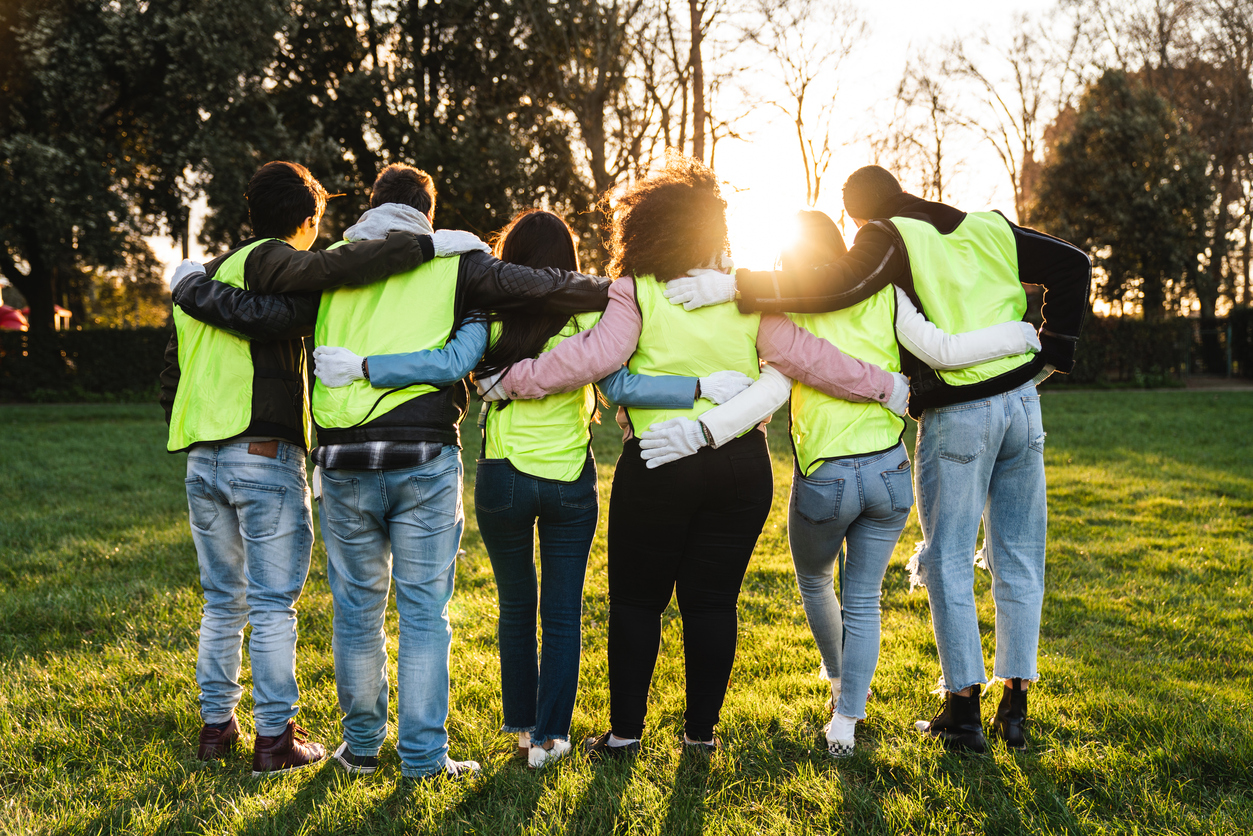 Image of a bunch of young volunteers in a park wearing high visibility vests.