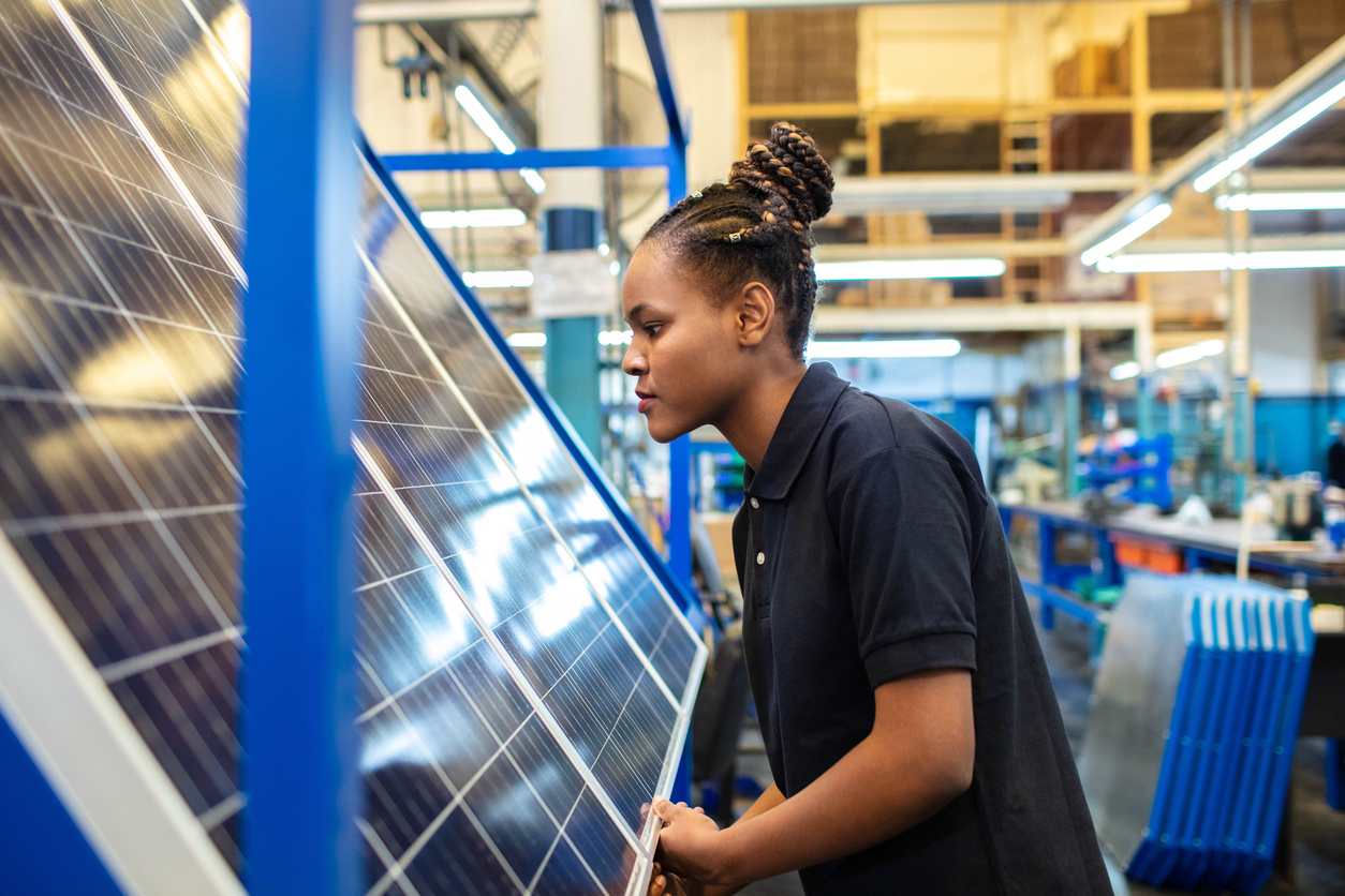 Woman quality engineer examining solar panels in factory.