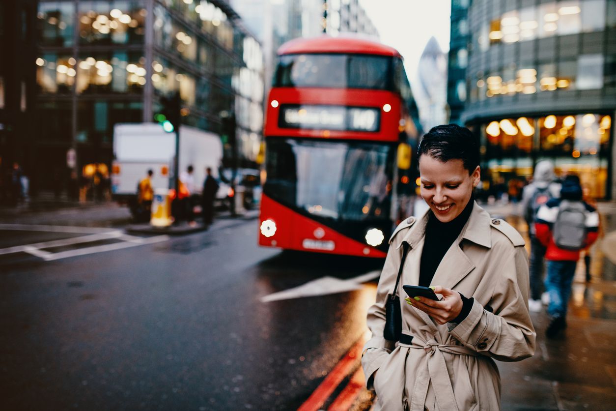 Woman checks her smartphone whilst commuting in London City Centre