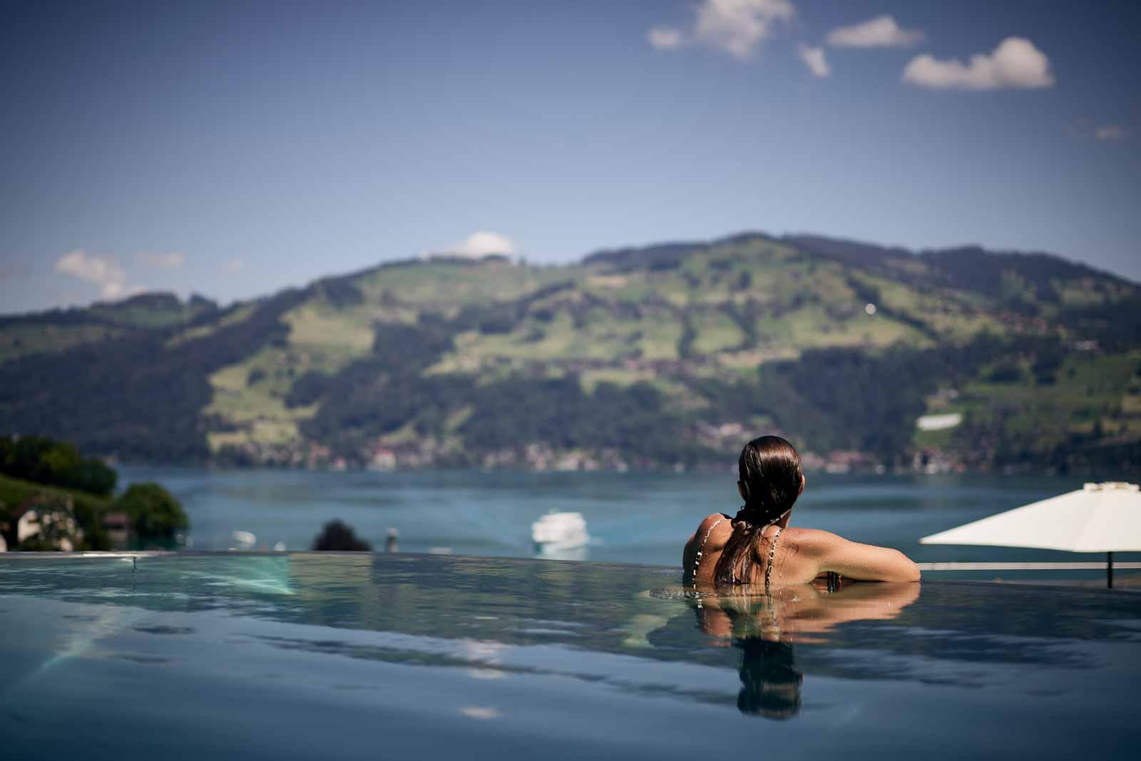 Woman in infinity pool with view of Lake Thun