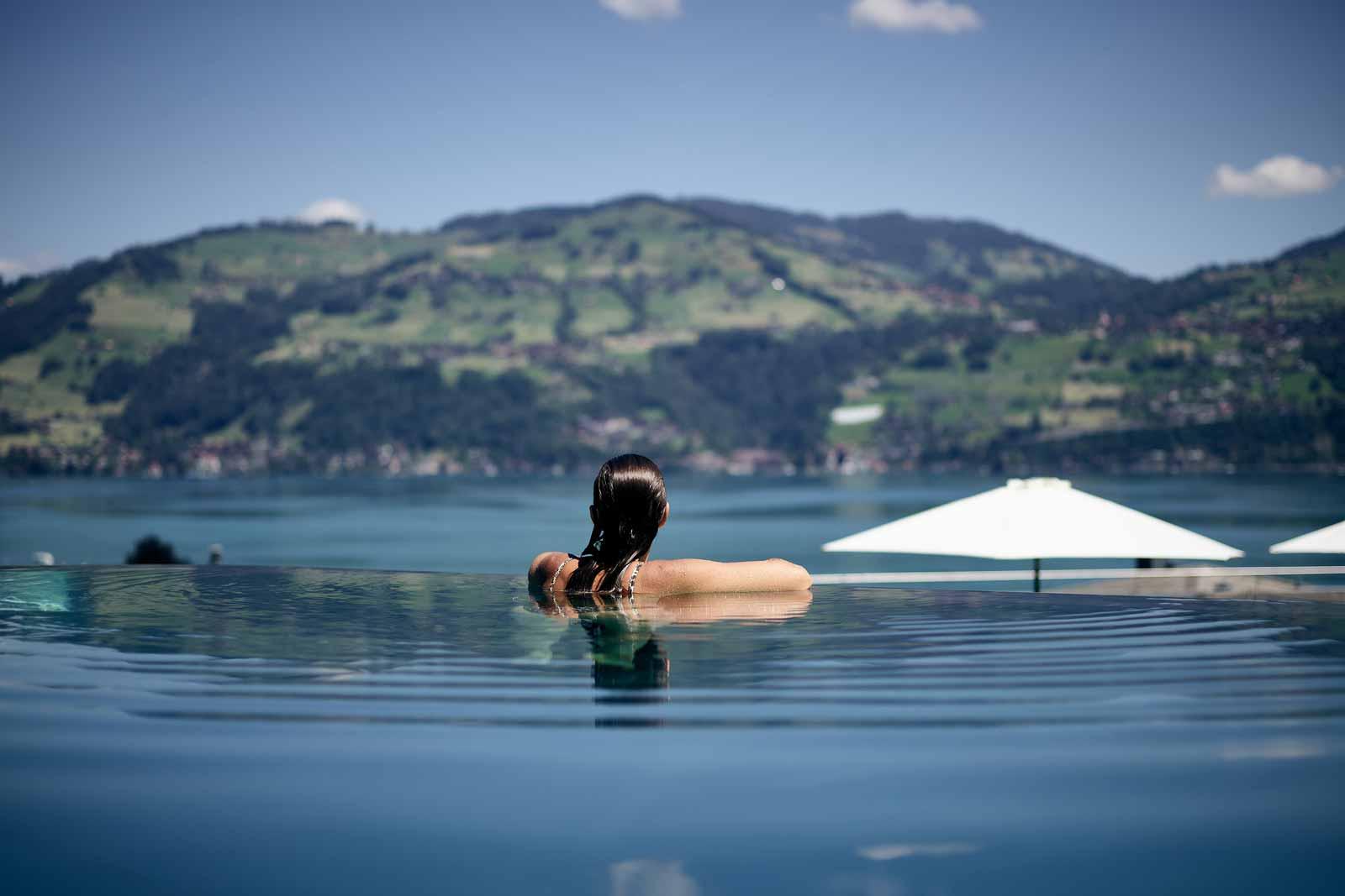 Frau im Infinity Pool mit Sicht auf den Thunersee