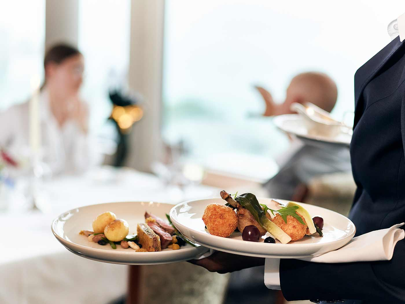 Restaurantbedienung bringt Teller zum Tisch