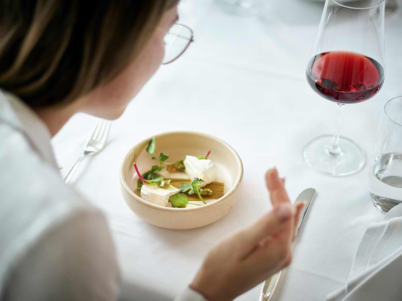 Frau riecht an einem Salat mit Käse