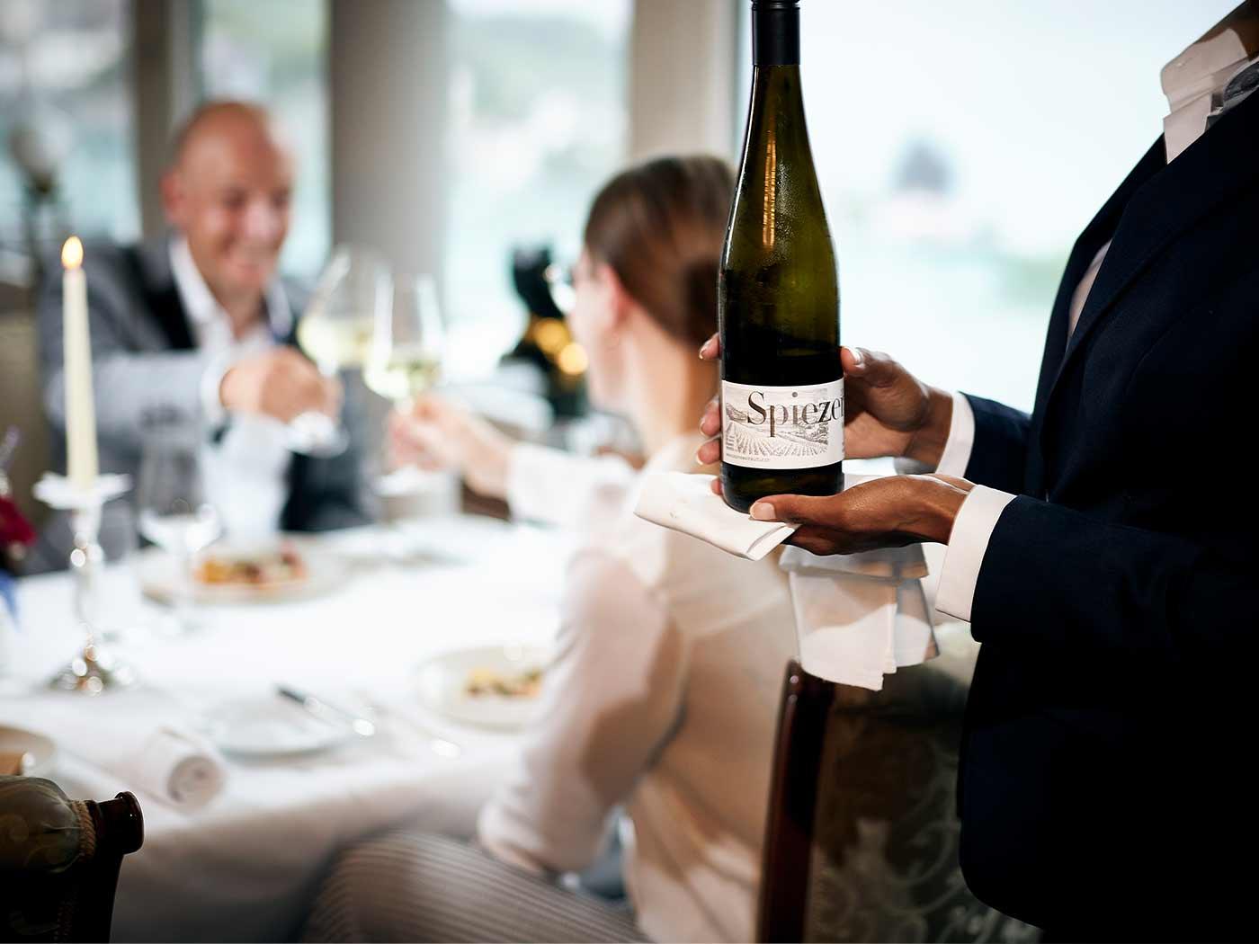 Restaurantbedienung bringt Flasche Wein an den Tisch