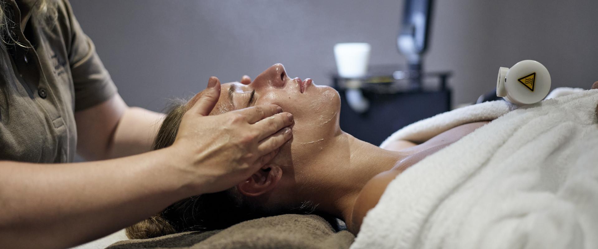 Oberkörper einer Frau mit Händen der Masseurin