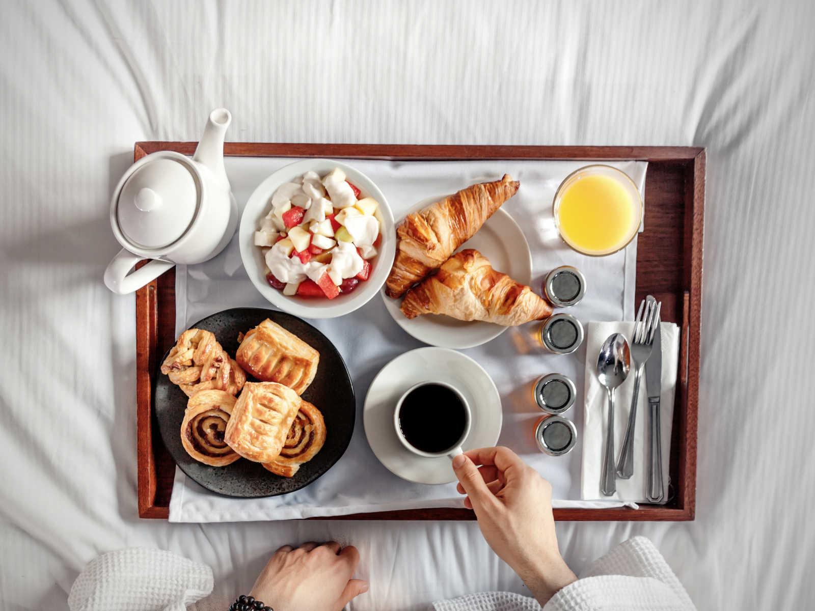 Tablet mit Kaffee, Croissants, Früchten