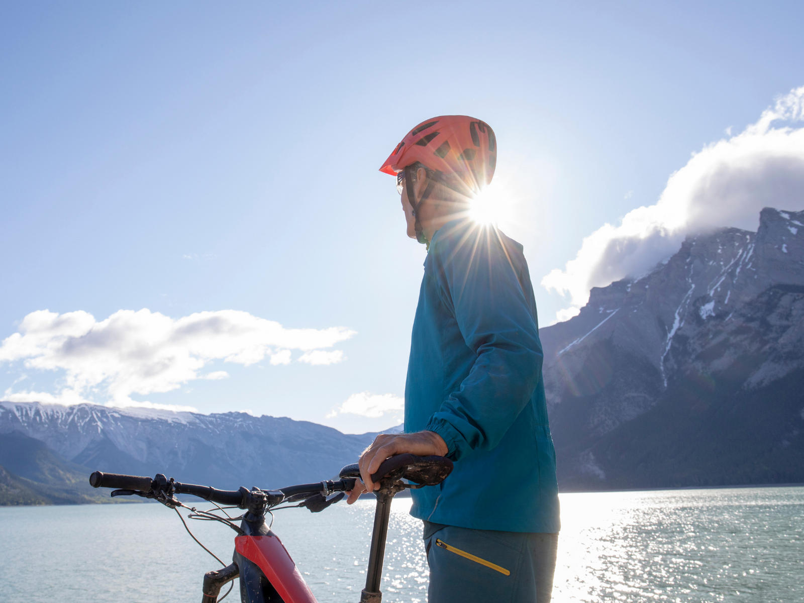 Man with bicycle in front of lake with mountains