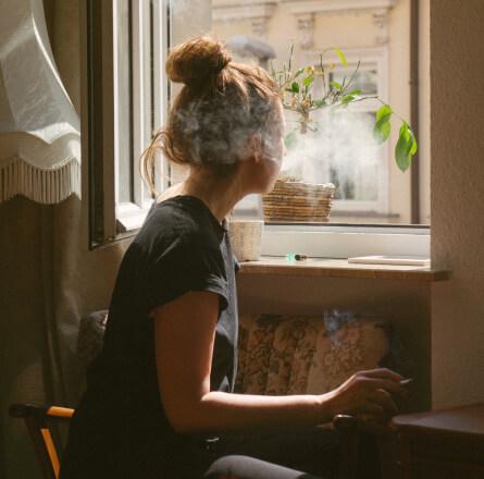 Kobieta paląca papierosa i patrząca przez okno