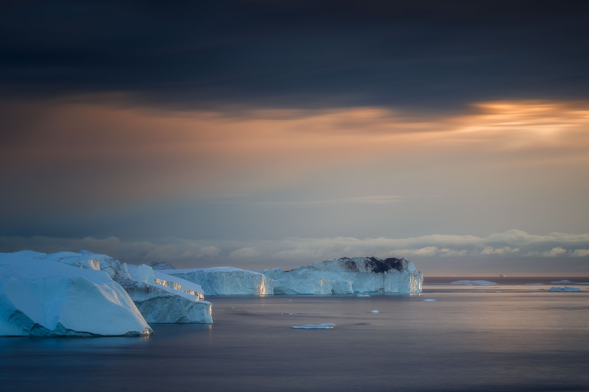 Golden hour over the sea with icebergs in the foreground