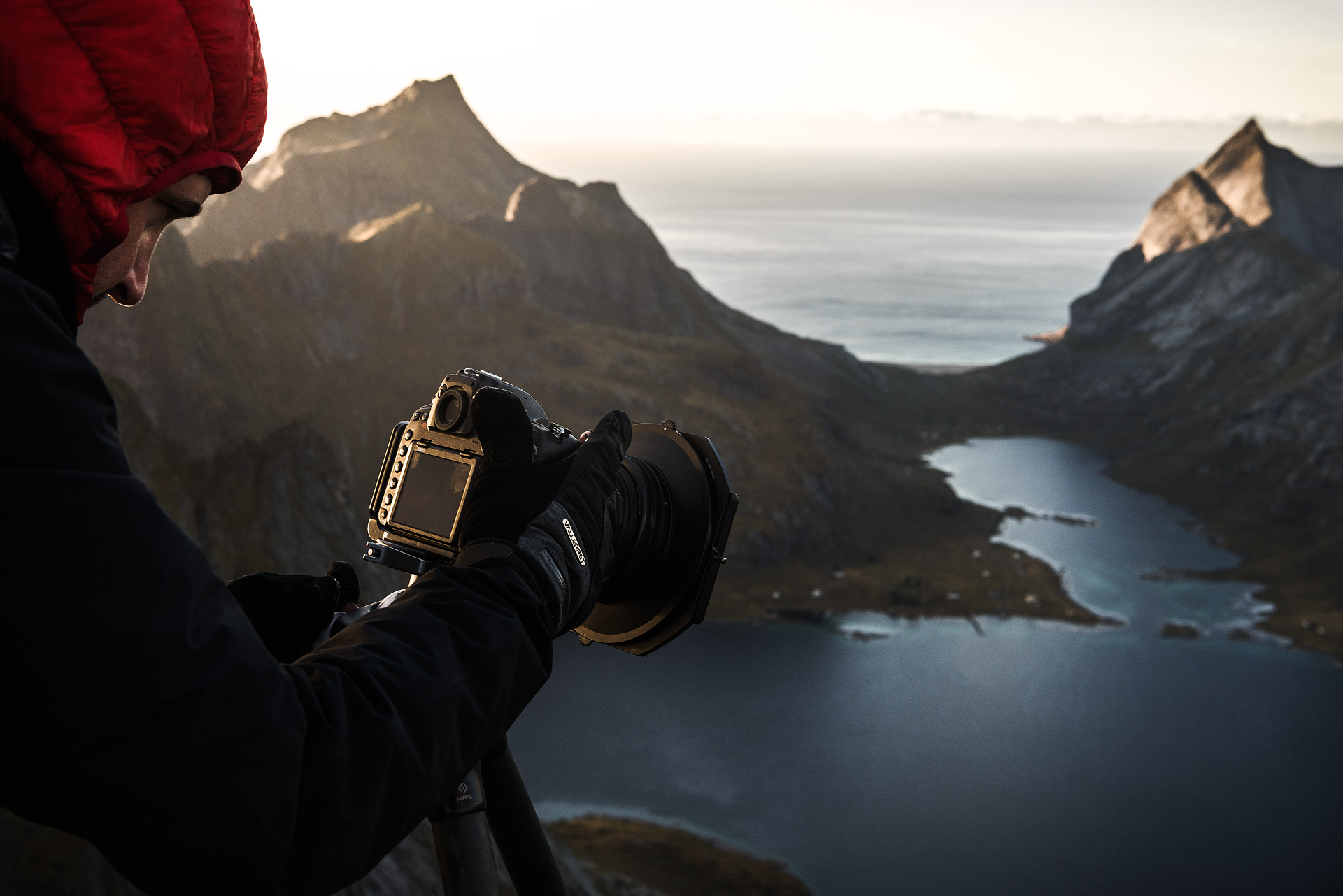 Photographer looking at the LCD view of their camera with a mountain landscape in the background