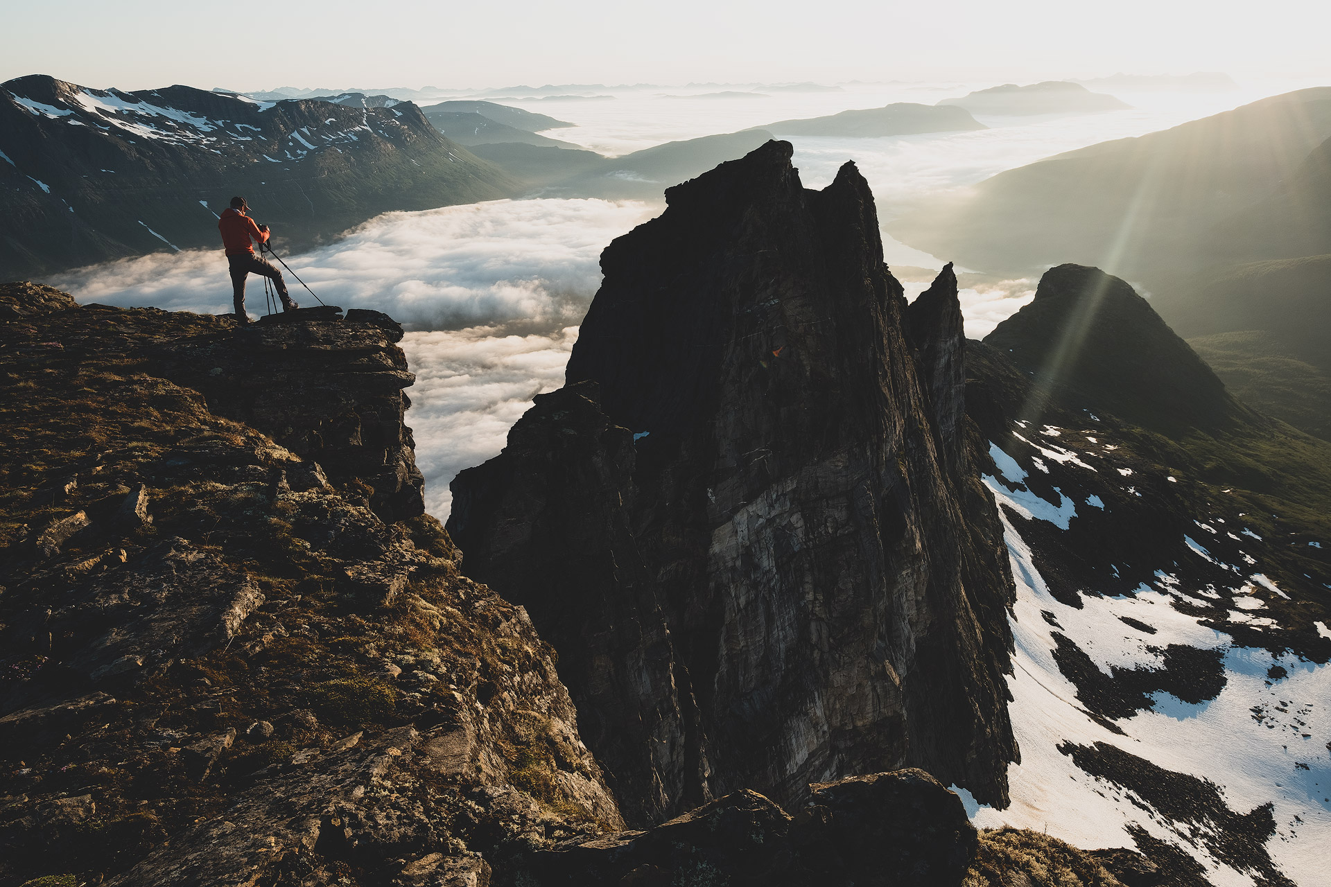 Photographer with a tripod taking a picture of an epic landscape