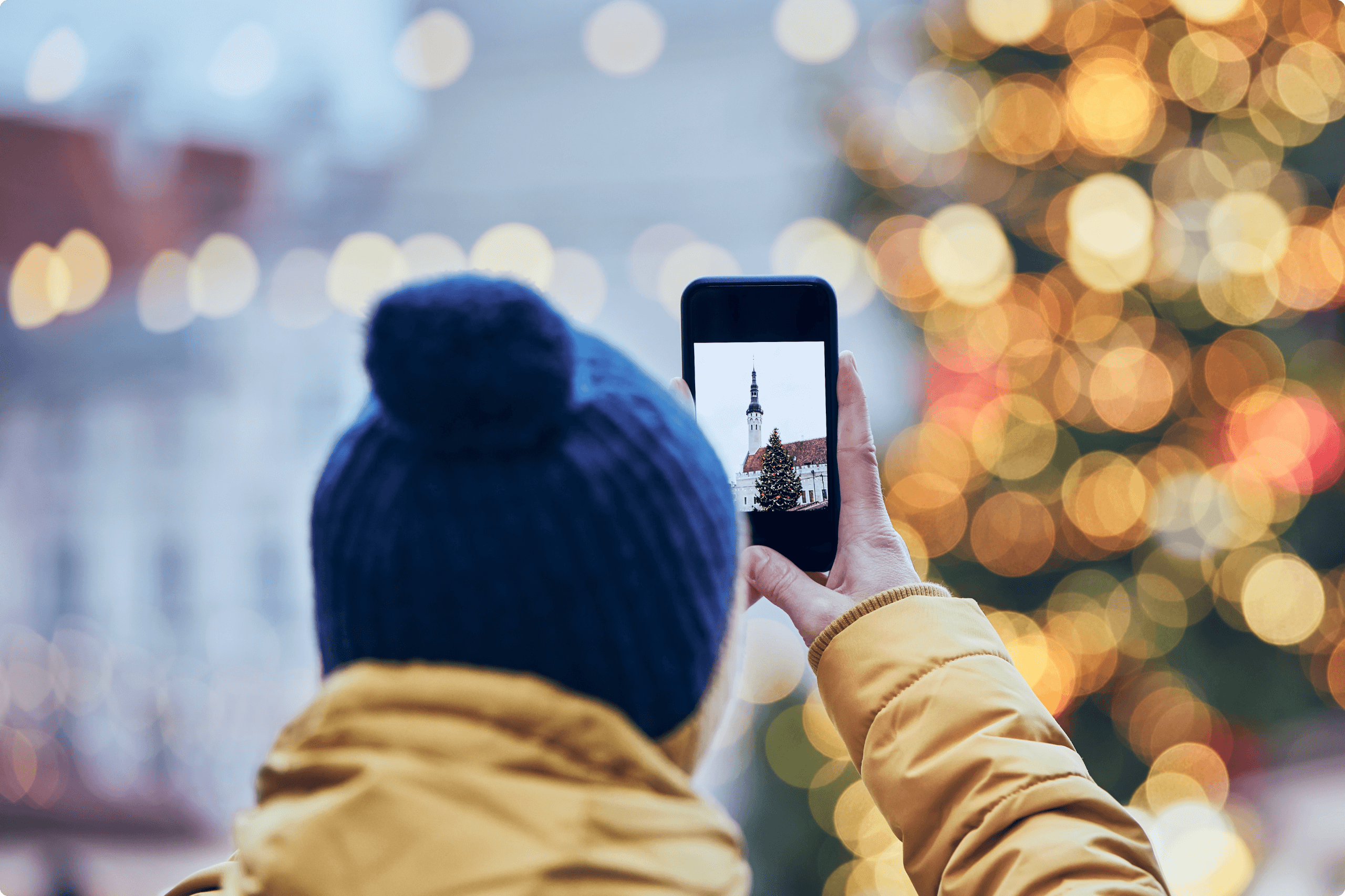 Photographer taking a picture of a Christmas tree with his smartphone