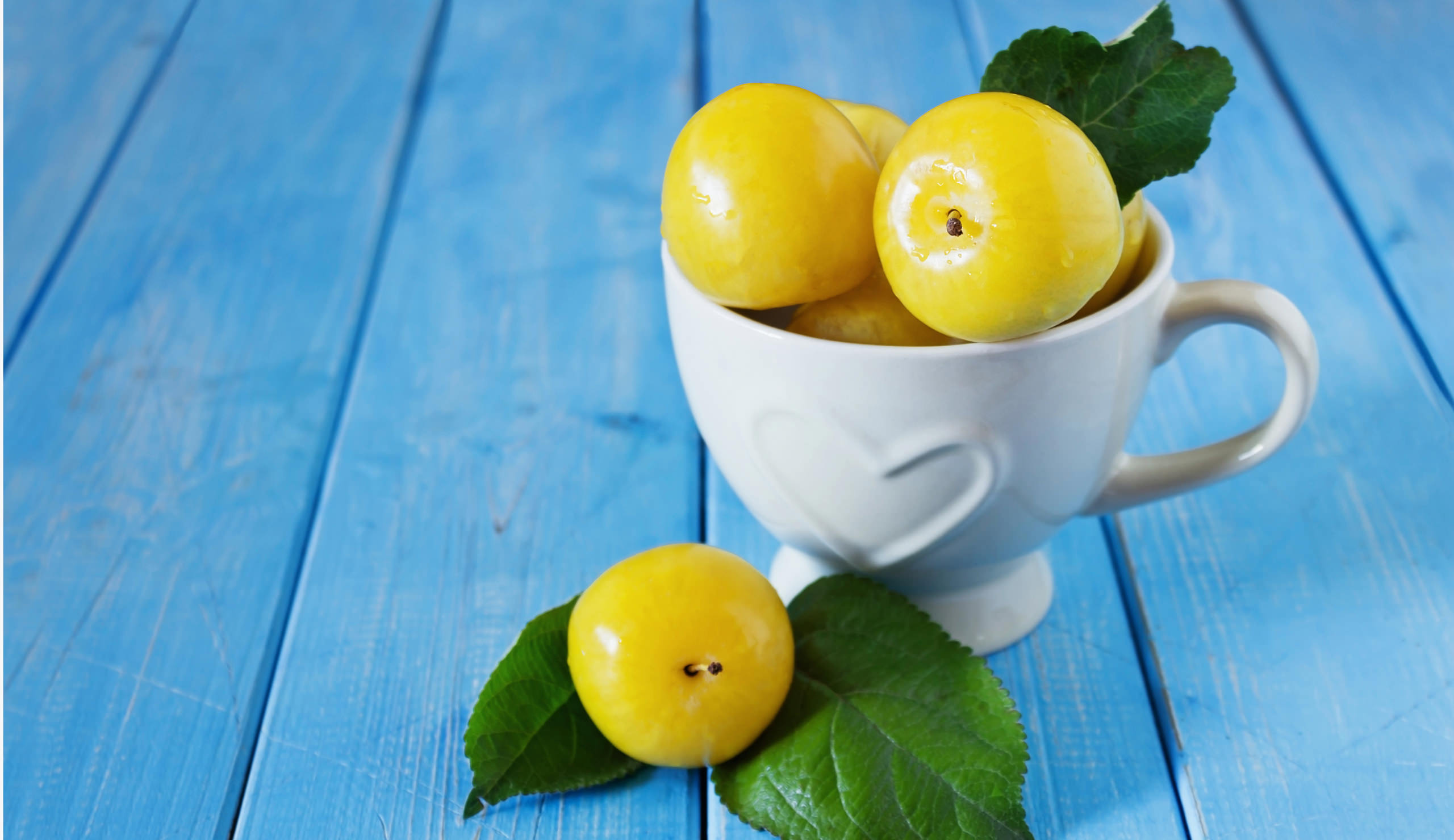 Lemons in a bowl on a wooden blue background