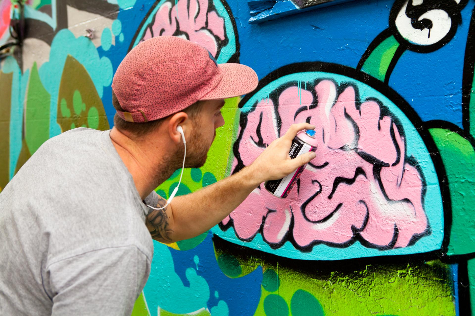 Man doing graffiit art with a spray paint can