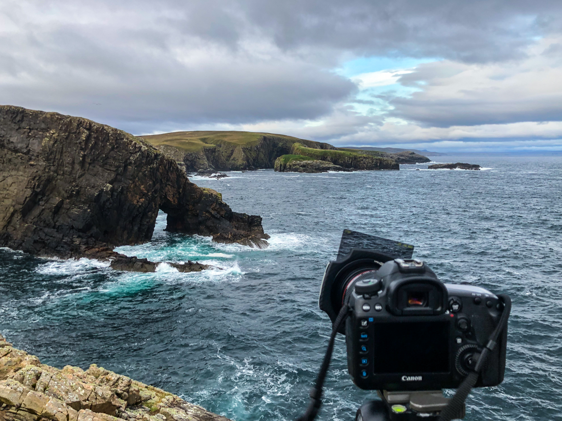 Camera on a tripod overlooking a rocky coast
